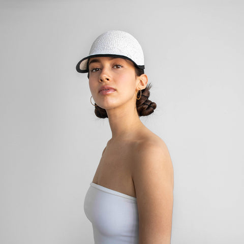The model is wearing the perfect fit CLAIRE cap in white.