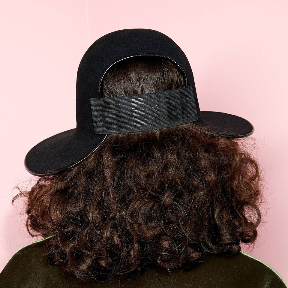 The curly hair model is wearing the felt hat Clever.