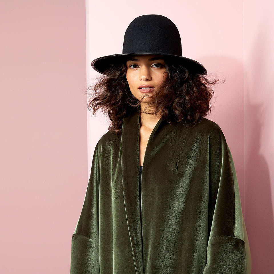 The model wears a green cape and the Clever Cropped Hat™ by Camille Côté.