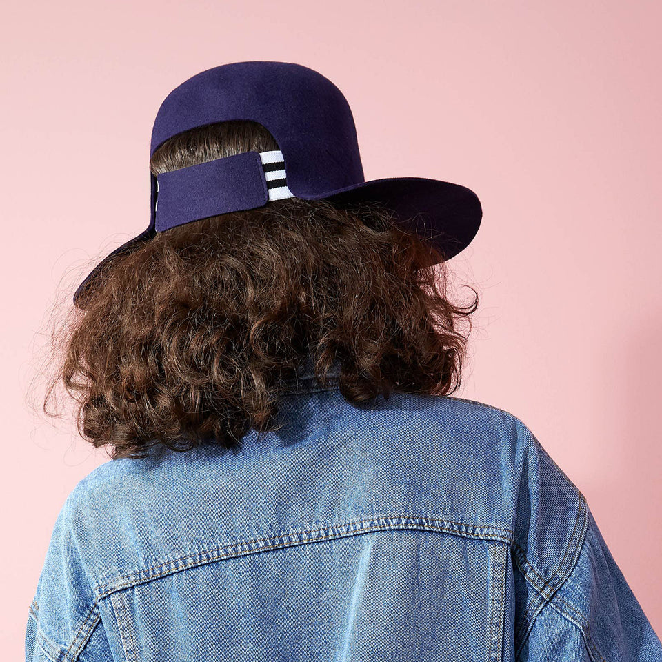 Curly hair model wearing Dean hat.