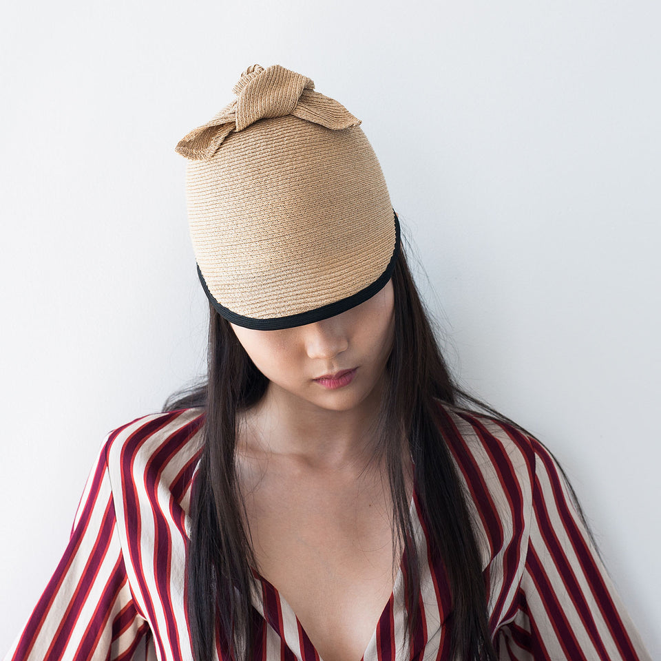 The model is wearing the tan Duchess summer hat by Camille Côté.