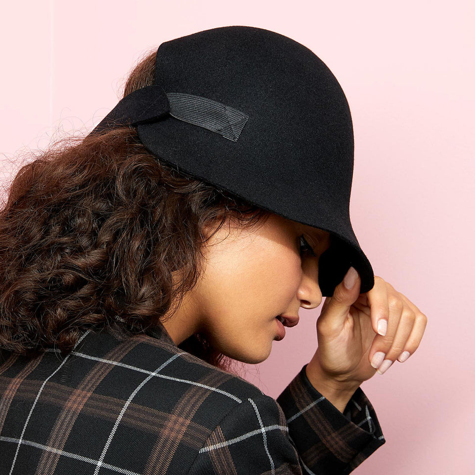 Curly hair model wearing the black Harlem hat.
