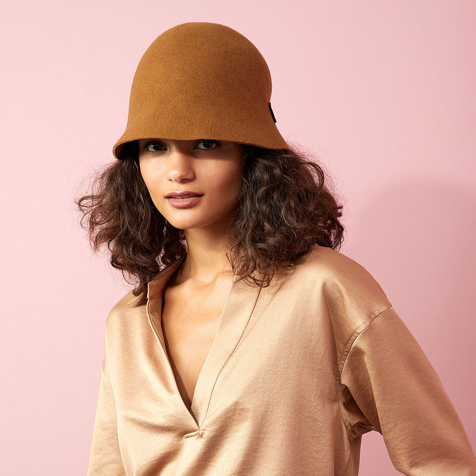 The model wears the cinnamon Harlem hat with a beige shiny blouse.