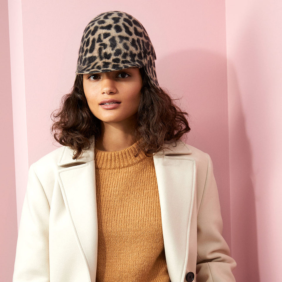 The curly hair model wearin the leopard printed hat Herman.