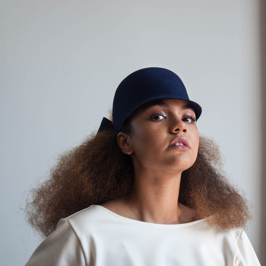 The natural hair model wearing the felt navy riding cap Jeanne.
