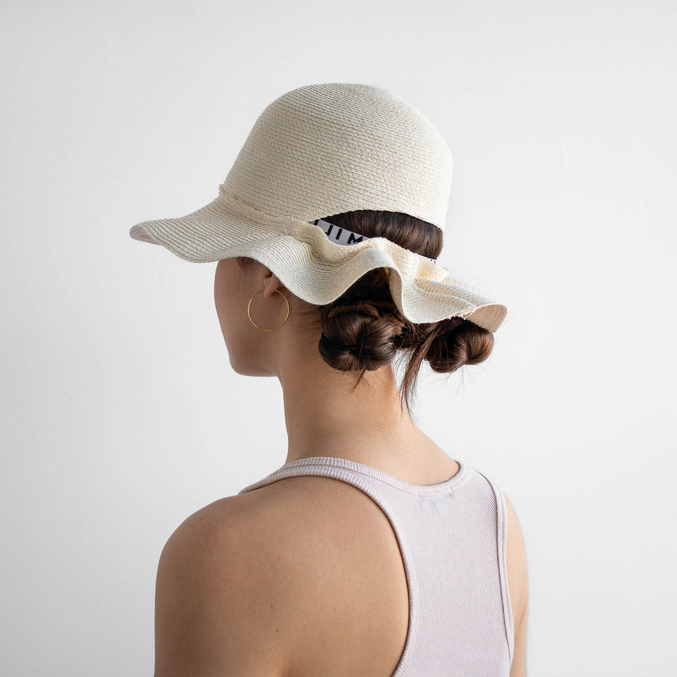 The model wears the cream Liberty summer bucket hat.