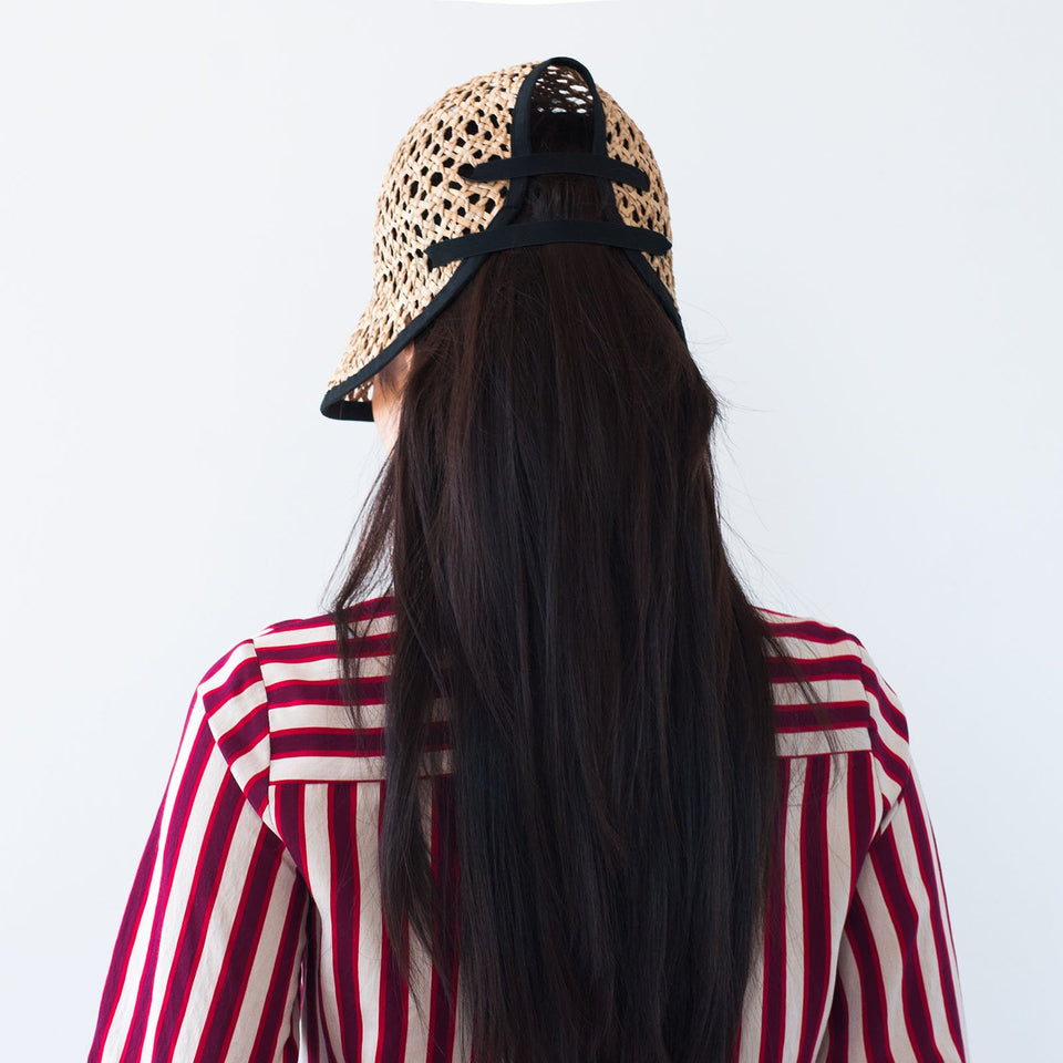 The model wears the natural straw hat Tsu by Camille Côté.