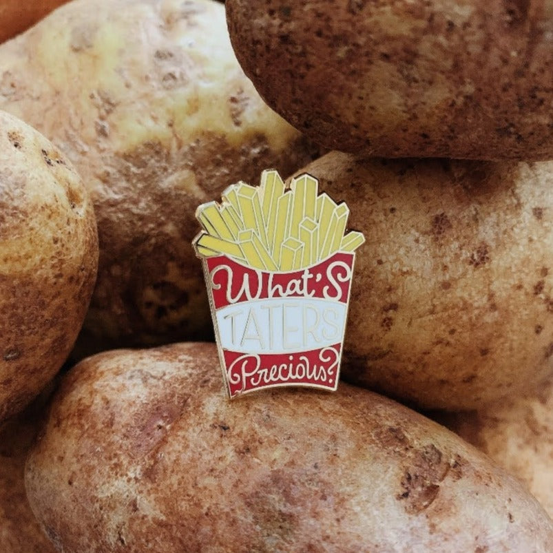 Red box of fries gold enamel pin that says What's Taters Precious on a pile of potatoes