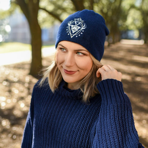 Young girl wearing a potter beanie in the woods