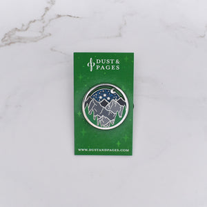 Glittery night sky enamel pin with a forest and mountains on a marble background