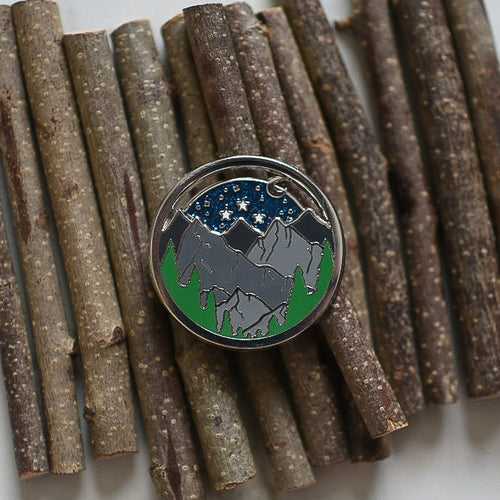 Glittery night sky with a forest and mountain enamel pin