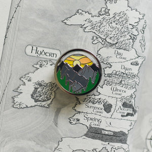 Dawn sky spinning enamel pin on a map of Prythian from ACOTAR