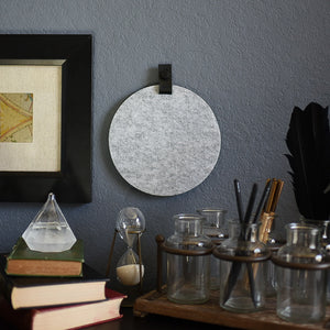 Round gray felt board with black tab for organization hanging on a living room wall