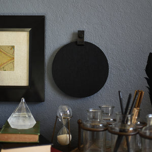 Round black felt board with black tab for organization hanging on a living room wall