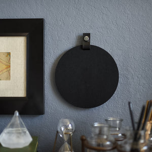 Round black felt board with black tab for organization hanging on an office wall