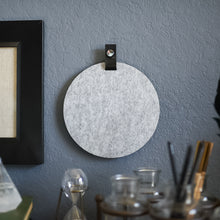Load image into Gallery viewer, Round gray felt board with black tab for organization hanging on a living room wall