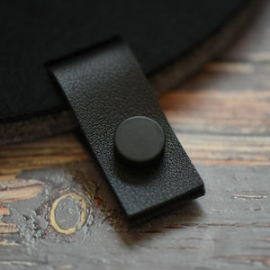 Faux leather black tab with black button attached to a felt board