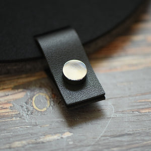Faux leather black tab with silver button attached to a felt board