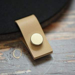 Faux leather cream tab with silver button attached to a felt board