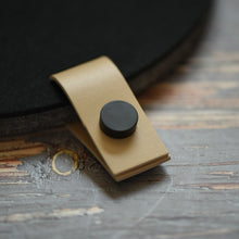 Load image into Gallery viewer, Faux leather cream tab with black button attached to a felt board