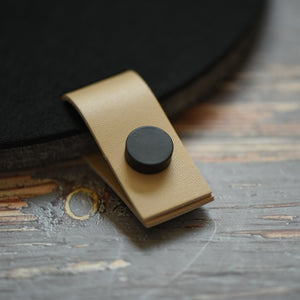 Faux leather cream tab with black button attached to a felt board