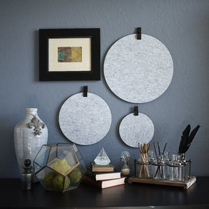 Three round gray felt boards with black tabs hanging on an office wall