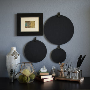 Three round felt boards for organization with black tabs hanging on a cozy wall