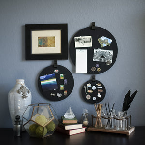 Three round black felt boards with black tabs for organization hanging on a living room wall