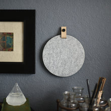 Load image into Gallery viewer, Round gray felt board with cream tab hanging on an office wall for organization