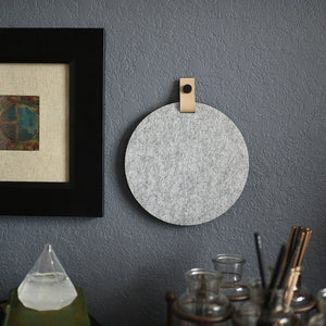 Round gray felt board with cream tab for organization hanging on a living room wall