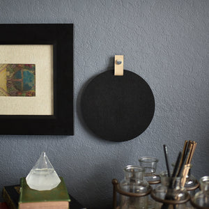 Round black felt board with cream tab for organization hanging on an office wall