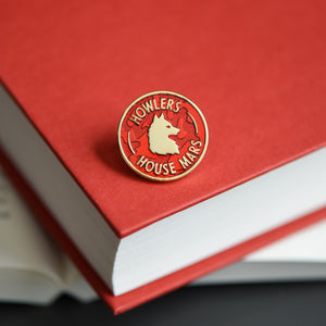 Red and gold circle membership style enamel pin with a wolf and howler house mars text on a red rising book