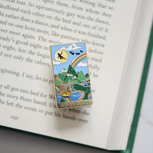 Gold Neverland landscape enamel pin with rainbow, moon, peter pan silhouette, and fairy ship details on an open book