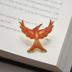 Mockingjay with red orange and yellow flame details enamel pin sitting on a book