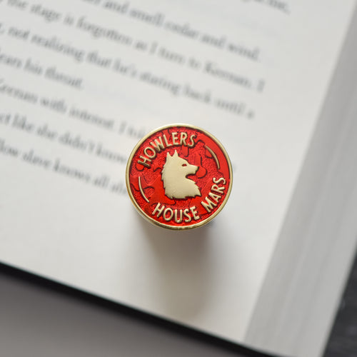 Red and gold circle membership style enamel pin with a wolf and howler house mars text