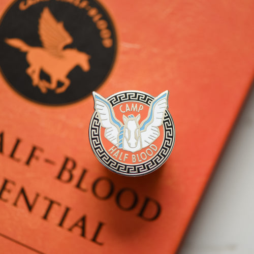 Pegasus horse inside a circle with camp half blood writing on an orange book
