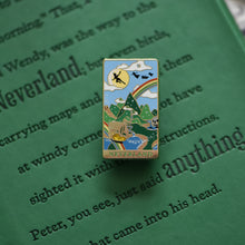 Load image into Gallery viewer, Gold Neverland landscape enamel pin with rainbow, moon, peter pan silhouette, and fairy ship details on green book