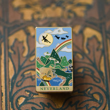 Load image into Gallery viewer, Gold Neverland landscape enamel pin with rainbow, moon, peter pan silhouette, and fairy ship details on an open book
