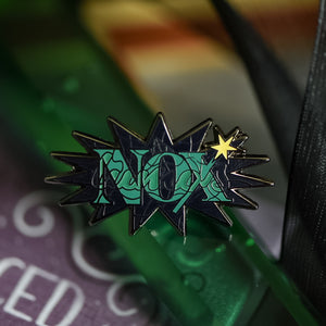 Black nickel enamel pin with Nox in green letters with glow in the dark lumos letters on a potion spell book