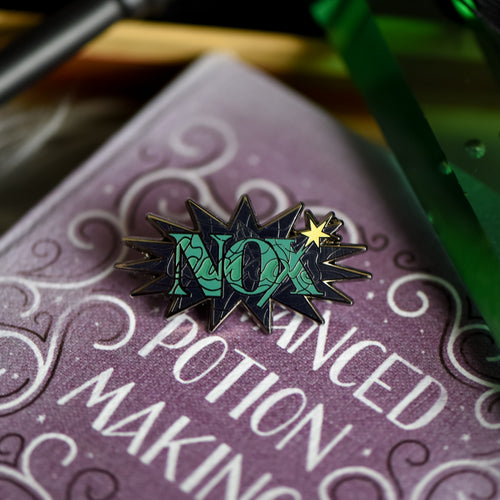 Black nickel enamel pin with Nox in green letters on a potion spell book