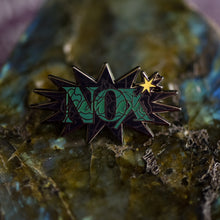 Load image into Gallery viewer, Black nickel enamel pin with Nox in green letters on a potion spell book