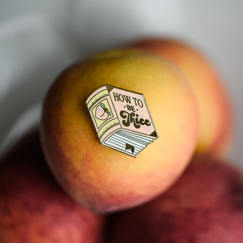 Peach book enamel pin with the title How to be Thicc on a stack of peaches