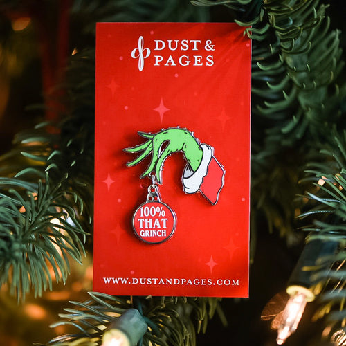 Enamel pin of grinch hand holding a red ornament with a Lizzo quote parody