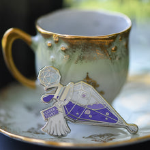 Load image into Gallery viewer, Purple and silver potion bottle enamel pin with a tag that says Reader Tears sitting on a teacup