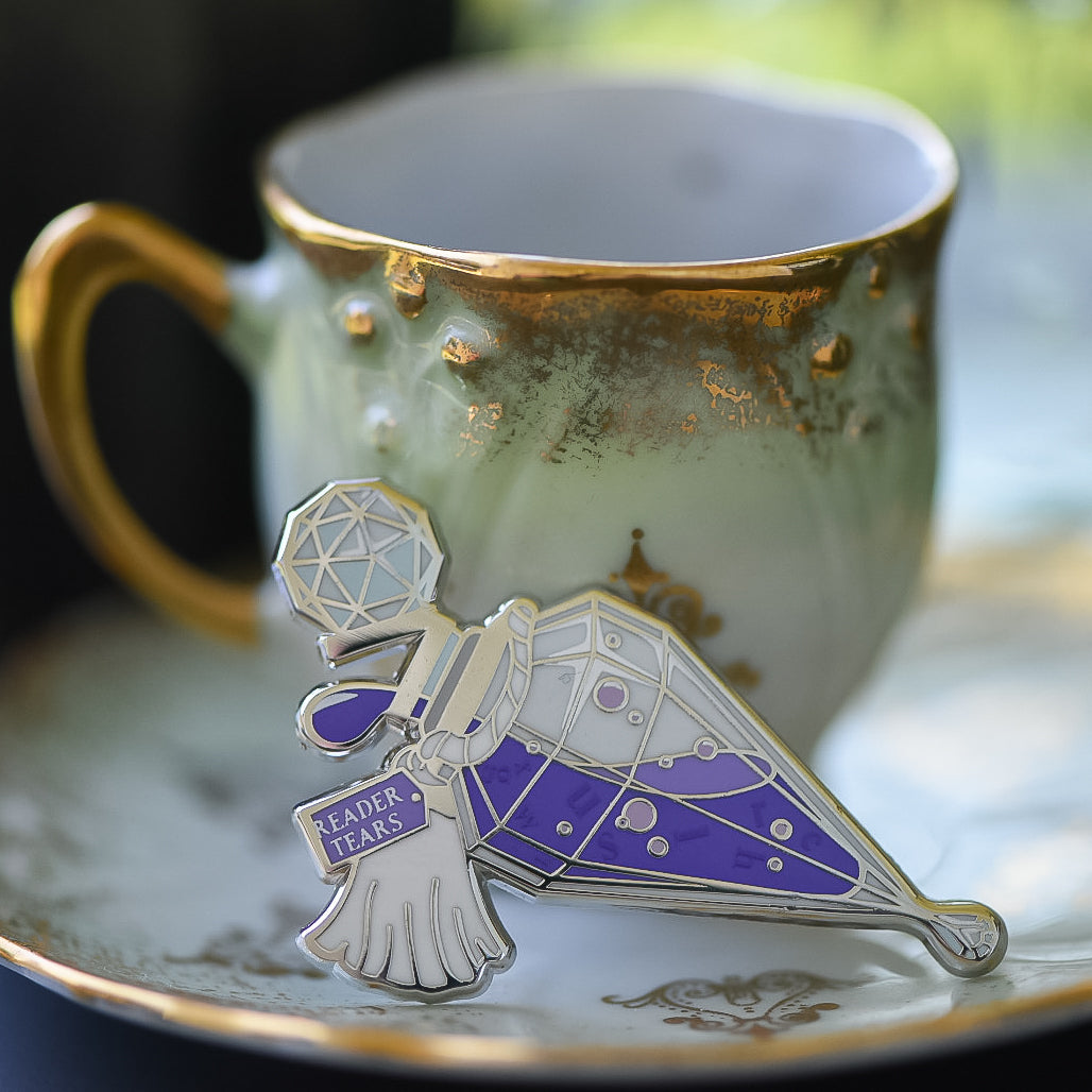 Purple and silver potion bottle enamel pin with a tag that says Reader Tears sitting on a teacup