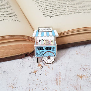 Cute pastel book shop cart enamel pin on an open book