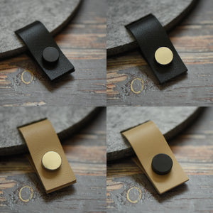 Faux leather hanging tabs with black button attached to a felt board for pin collections and organization