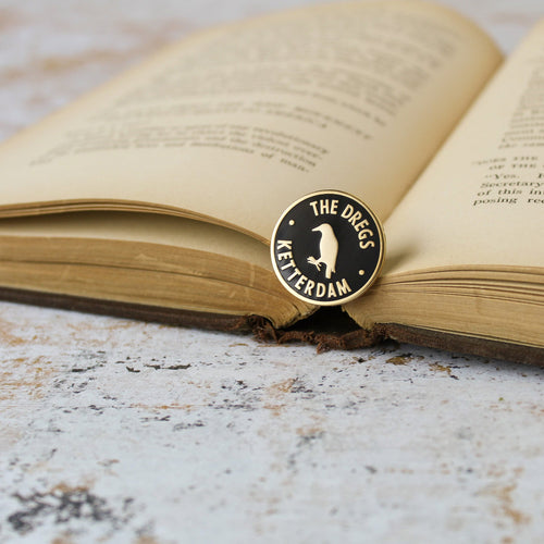 Black and matte gold crow inside a circle dregs membership style enamel pin on an open book