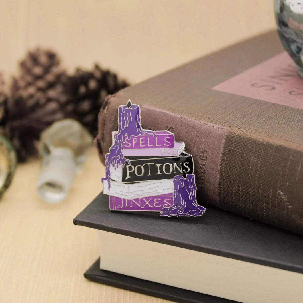 Purple witchcraft spellbook stack for potions and jinxes enamel pin
