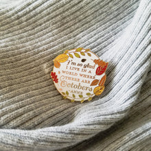 Load image into Gallery viewer, Round white fall enamel pin on a gray sweater